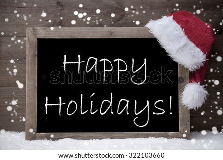 Gray Blackboard With Red Santa Hat On White Snow. English Text Happy Holidays. Snowy Atmosphere With Snowflakes. Christmas Decoration With Brown Vintage Wooden Background. Black And White - stock photo