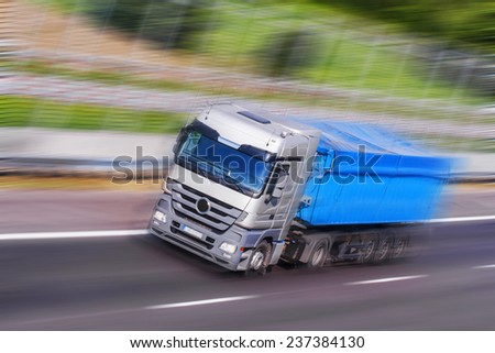 Gray-Blue Truck on a fast express road, motion blur - stock photo