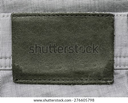 gray-brown  leather label on light gray jeans background