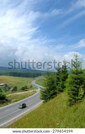 Gray bus is moving along the road with carriageway marking. The road is surrounded with meadows and forest. Fir-tree and grass are in the foreground, blue sky with clouds are in the backgrpound. - stock photo