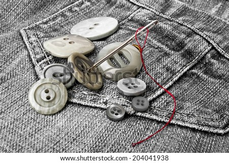Gray buttons with needle on denim - stock photo
