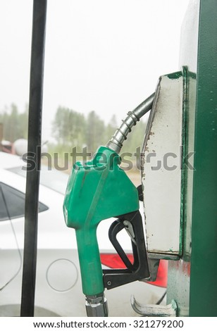 Gray car on a gas station  Green Fuel dispenser or nozzle against modern auto and sky  - stock photo