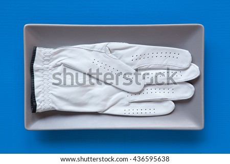 Gray ceramic dish with golf glove on over blue  background, rectangle dish - stock photo