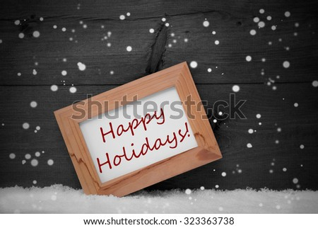 Gray Christmas Card With Brown Picture Frame On White Snow With Snowflakes. English Text Happy Holidays. Rustic Wooden, Retro Vintage Background. Black And White - stock photo