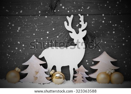 Gray Christmas Card With Golden Festive Decoration On Snow. White Reindeer, Christmas Ball, Tree And Snowflakes. Brown, Rustic, Vintage Wooden Background. Copy Space For Advertisement. Black And White - stock photo