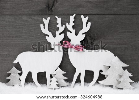 Gray Christmas Decoration With Reindeer Couple In Love On White Snow. Red Ribbon, Christmas Tree. Rustic, Vintage Wooden Background. Christmas Card For Seasons Greetings. Black And White Image - stock photo