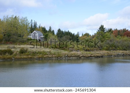 gray clapboard house near the coast in rural Maine during a New England autumn - stock photo