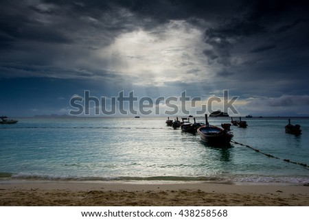 Gray clouds over the blue sea and  the boat on the beach at the sea coast .Lipe , Thailand.