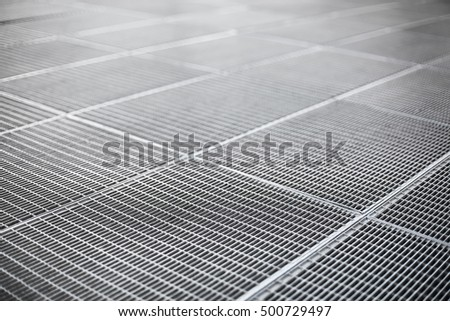 Gray color metal ventilation grille on a sidewalk with shallow depth of field