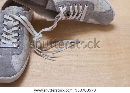 gray color sneakers on the wooden background