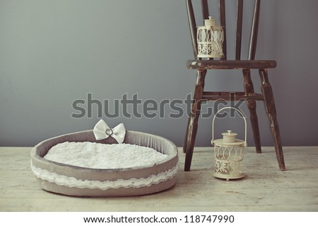 Gray dog or cat pet bed with chair in home interior - stock photo