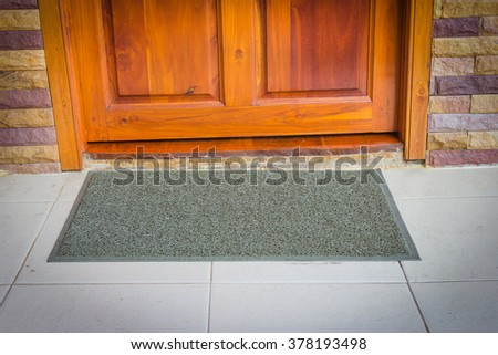 gray door mat  with close door