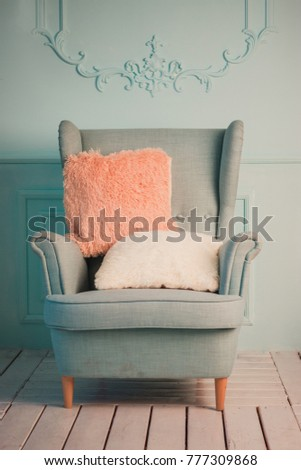 Gray easy armchair with pink scarf, pillow and book next to bed