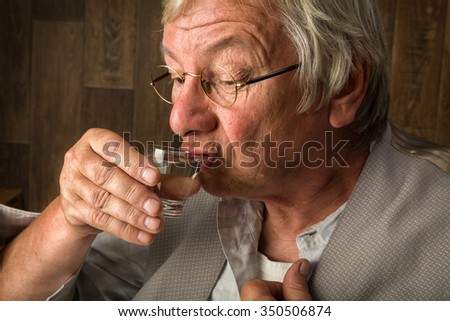 Gray elderly man enjoying a jenever drink in a shot glass - stock photo