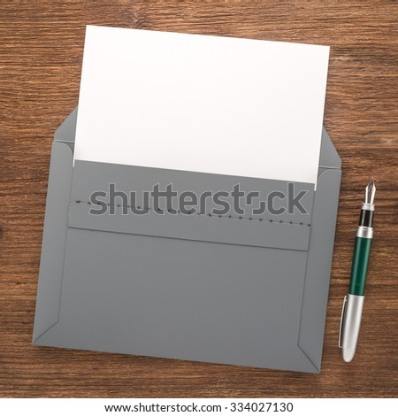 Gray envelope with white paper and pen