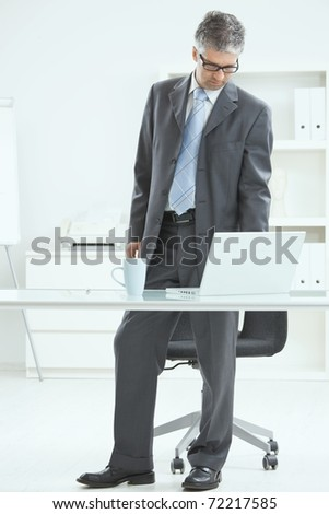 Gray haired businessman using laptop computer, standing behind office desk, working. ? - stock photo