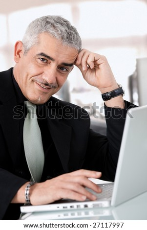 Gray haired creative director working on laptop computer at office, smiling. - stock photo