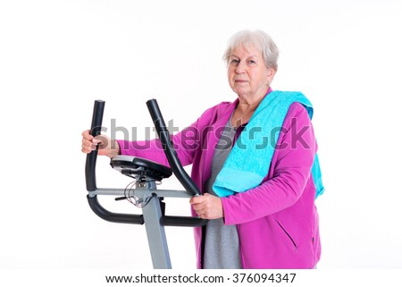 gray-haired female senior trains with fitness machine