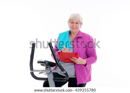 gray-haired female senior with clipboard train with fitness machine - stock photo