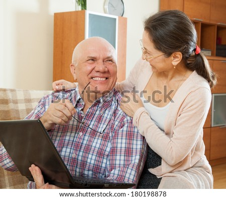 gray-haired man and mature woman with laptop   at home - stock photo