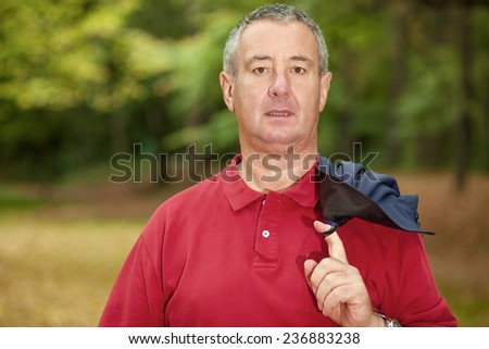 Gray-haired man in the autumn walk - stock photo