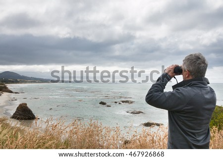 Gray haired man looks in binocular across ocean bay, New Zealand