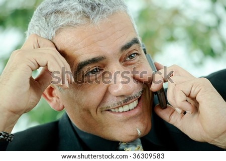 Gray haired mature businessman calling on mobile phone, smiling. - stock photo