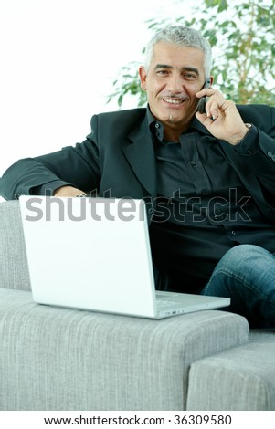 Gray haired mature businessman sitting on couch working on laptop computertalking on mobile phone, happy, smiling.