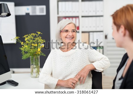 Gray Haired Middle Aged Office Woman Listening to her Young Colleague Talking to Her Inside the Office.
