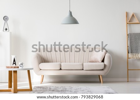 Gray lamp above beige couch in sophisticated living room interior with ladder and wooden round table