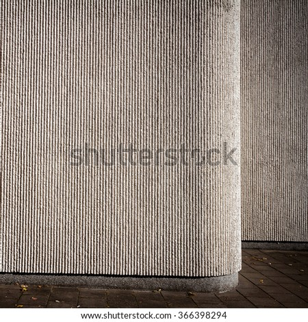 Gray lined plaster street wall and a pavement   - stock photo