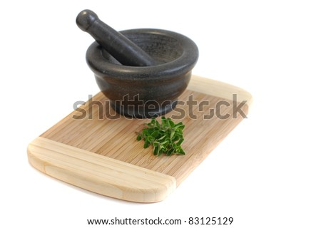 Gray mortar and freshly picked oregano on a wooden cutting desk on a white background