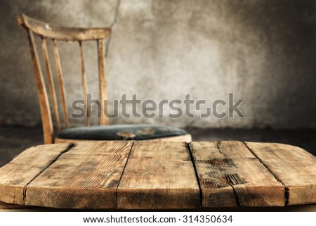 gray old worn wall in interior with retro chair and shabby wooden desk space  - stock photo