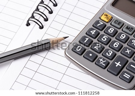 Gray pencil and calculator lying on opened account book - stock photo