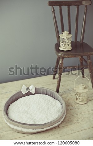 Gray pet bed with bowtie and chair with lantern in interior - stock photo