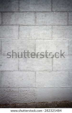 Gray plastered street wall and a pavement
