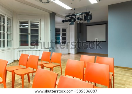 Gray presentation room with orange chairs
