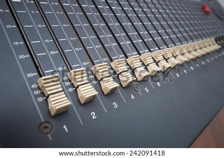 gray professional studio mixing console closeup shot - stock photo