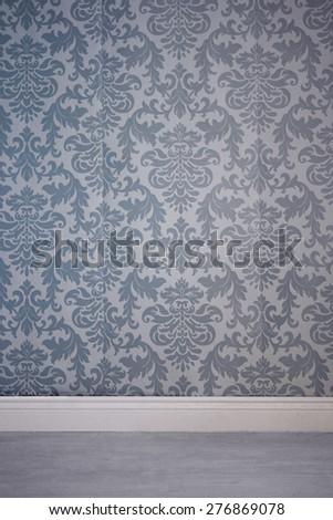 Gray residential interior with wall covered by wallpaper with seamless floral damask pattern and empty floor - stock photo