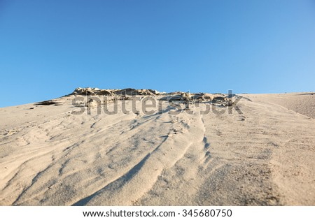 Gray sand dunes and the blue sky. - stock photo