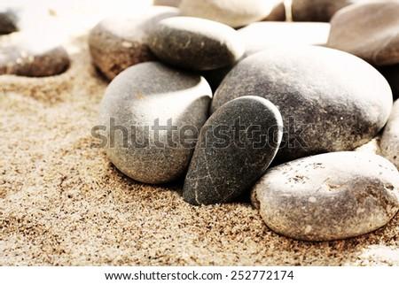 Gray sea pebbles on sand background - stock photo