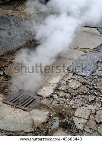 gray smoke rising from a sewer's rain drain at old street in Sarajevo, Bosnia - stock photo