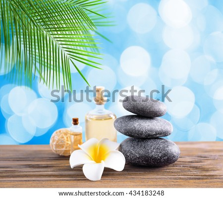 Gray spa stones with oil on light blue background - stock photo