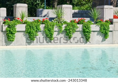 Gray stone wall by a pool in the garden - stock photo
