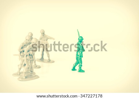 Gray toy soldiers pointing and bullying a green toy soldier - stock photo
