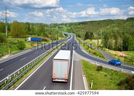 Gray truck departing on an asphalt highway between lush forests in the countryside. In the distance the bridge and Electronic toll gate. Sunny spring day with dramatic white clouds. View from above. - stock photo