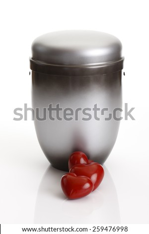 Gray urn and two hearts on white background - stock photo