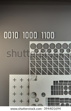 Gray wall with several white volumetric numbers on it, white ornamental panel and white panel with black prints. Close-up photo.