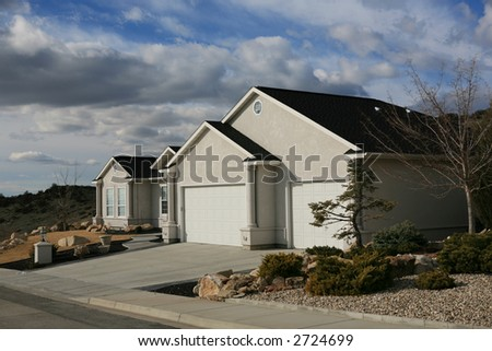Gray white stucco house from the side with gray clouds - stock photo
