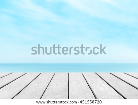 Gray wood floor with white blur surfing wave background. Blue water and sky bright. Summer nature wallpaper blurred of sea daytime. Focus to top table in the foreground. Timber pattern texture stage. - stock photo